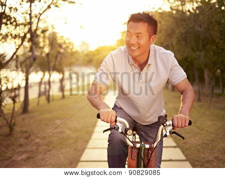 Asian Man Enjoying Bike Ride Outdoors At Sunset In Park