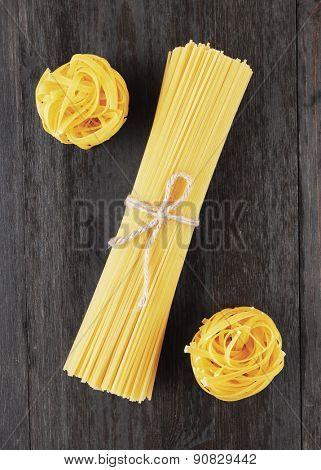 Tagliatelle and spaghetti italian pasta on wood background