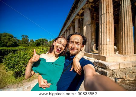 Young couple taking selfie picture with Hephaistos temple on background in Agora near Acropolis