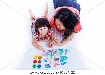 Little Asian (thai) Girl Painting With Her Mother Near By, On White Background. Studio Shot. Top Vie
