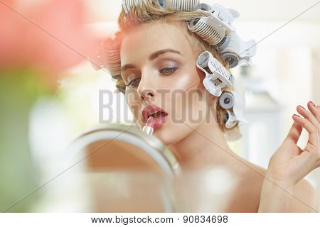 Beautiful young blonde lady doing make-up
