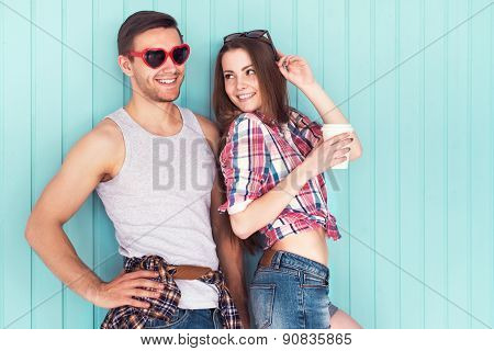 Happy couple friends wearing funny sunglasses heart shape in summer jeanswear street urban casual st