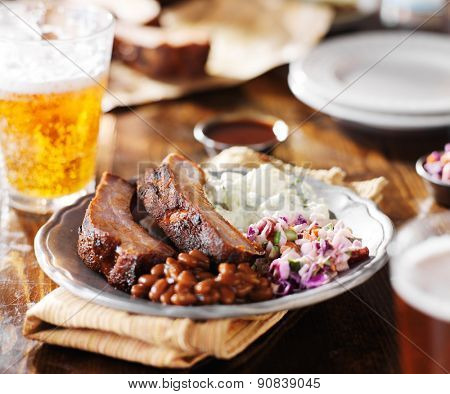 barbecued spare ribs with coleslaw, potato salad, baked beans, and beer