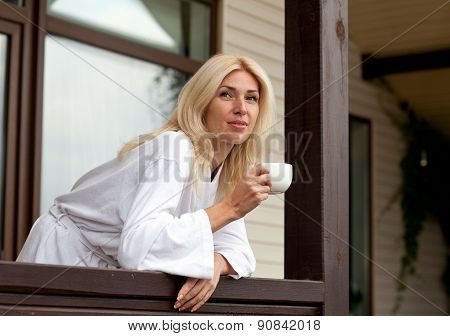 Young Woman Drinking Morning Coffee on Porch