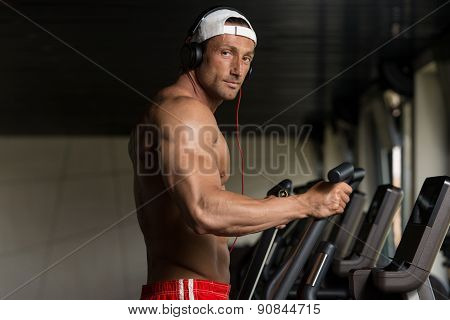 Mature Man Doing Aerobics Elliptical Walker In Gym