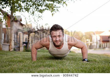 Push ups sport fitness man doing push-ups. Male athlete exercising push up outside in sunny sunshine