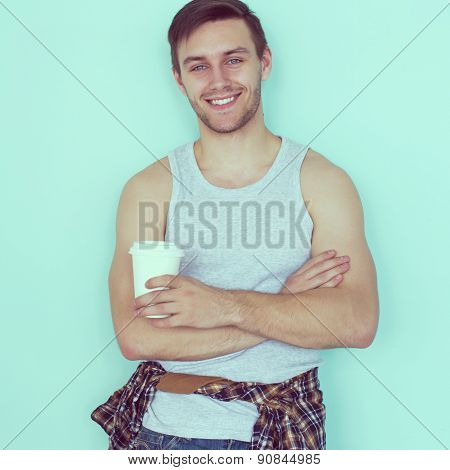 Portrait young man holding paper cup of coffee city street casual urban style looking at camera stan