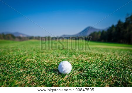 Golf Ball On Green Area With Green Grass Ahead And Mountains In Background