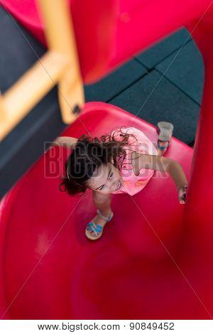Girl On Playground Slide