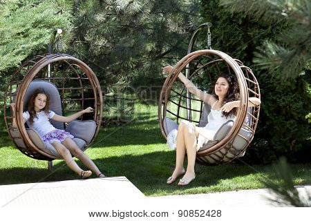 Woman and young girl sitting on patio