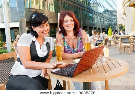 Two middle-aged women sitting in a cafe in downtown