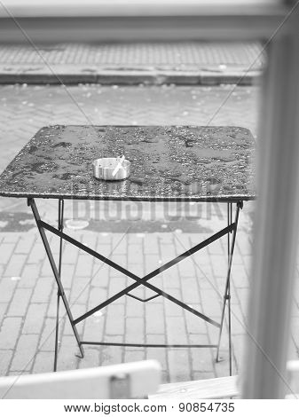 Empty outdoor table with ash tray ofter shower