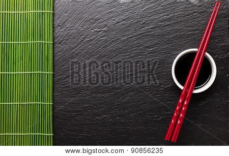 Japanese sushi chopsticks over soy sauce bowl on black stone background. Top view with copy space