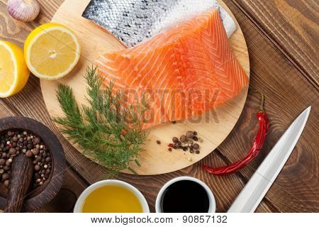 Salmon, spices and condiments on wooden table. Top view