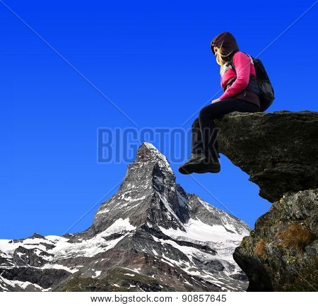 Girl sitting on a rock, in the background Matterhorn - Pennine Alps, Switzerland.