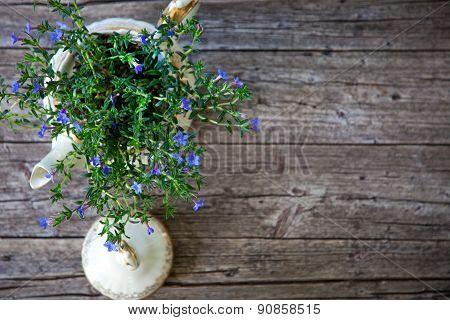 Bouquet Of Flowers In Tea Pot On Wooden Planks