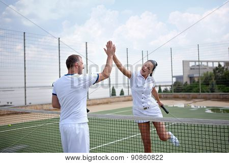 Couple handshaking at the tennis court after a match