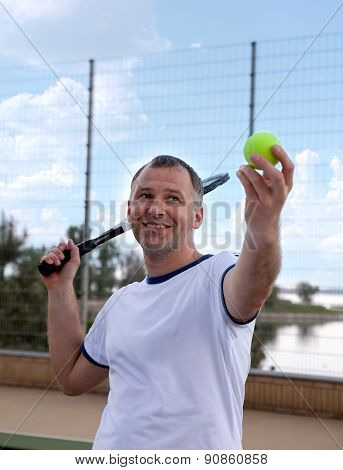 Male tennis player holding racquet on hard court