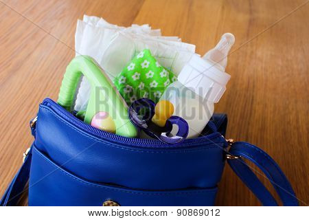 Women's handbag with items to care for the child: bottle of milk, disposable diapers, rattle, pacifi