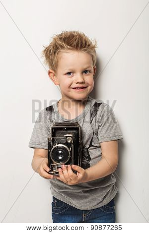 Young photographer. Little boy hold vintage camera