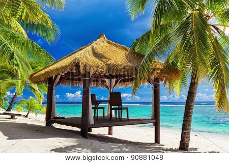 Tropical gazebo and two chairs on an sandy island beach with coconut palm trees