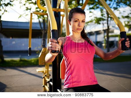 Woman Exercising Her Upper Body Using Weights Machine.