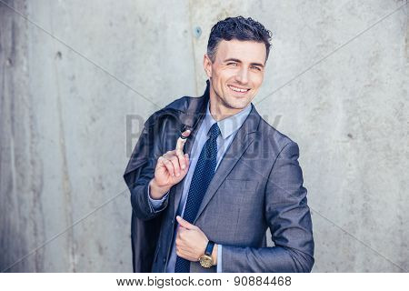 Portrait of a happy businessman standing over concrete wall and holding jacket on shoulder. Looking at camera