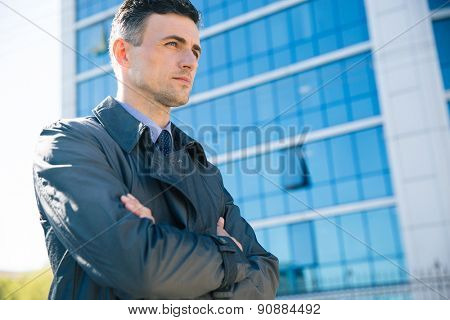 Portrait of a confident businessman standing with arms folded outdoors. Glass building on background
