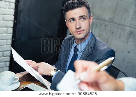 Handsome man making order at restaurant