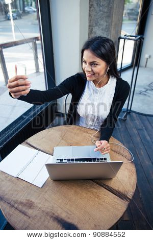 Cheerful businesswoman making selfie photo on smartphone in cafe