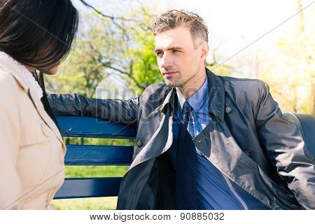 Portrait of a beautiful couple talking on the bench outdoors. Looking at each other