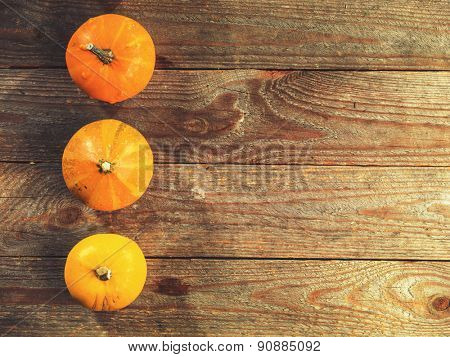 Autumn background with pumpkins and colored leaves on wooden board