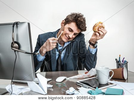 Young Business Man Talking On The Phone While Holding Burger In One Hand And Pencil In The Other Loo