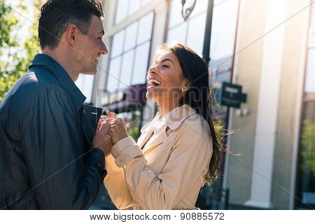 Portrait of a happy young couple flirting and looking to each other outdoors