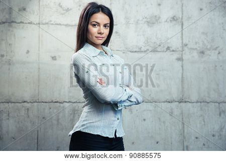 Portrait of a happy businesswoman standing with arms folded over concrete wall and looking at camera