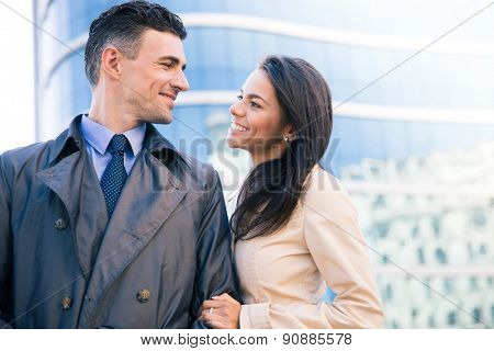 Happy woman and man flirting outdoors with glass building on background