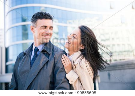 Portrait of a laughing couple flirting outdoors with glass building on background