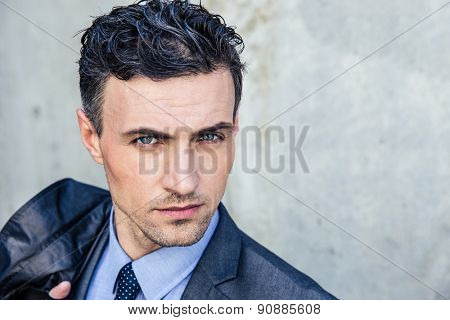 Portrait of a handsome businessman standing over concrete wall and looking at camera