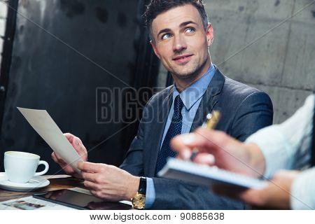 Happy handsome man making order at restaurant