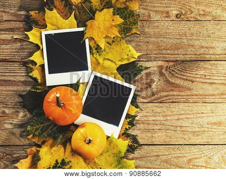 autumn background with colored leaves, pumpkin and old photo cards on wooden board
