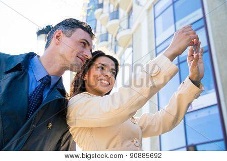 Happy beautiful couple making selfie photo on smartphone outdoors