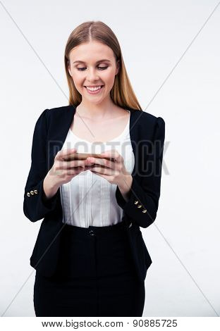 Happy young businesswoman using her smartphone over gray background