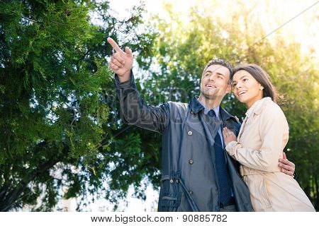 Smiling man pointing on something to his girlfriend outdoors. Trees on background