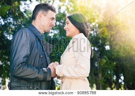 Smiling couple dating and flirting in park