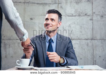 Smiling man giving bank card to female waiter in cafe