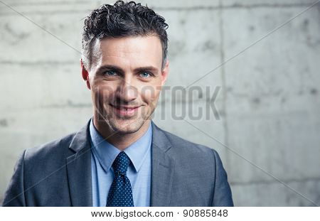 Portrait of a smiling businessman standing over concrete wall and looking at camera