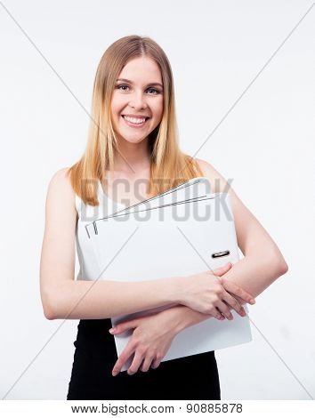 Happy young business woman holding folders over gray background and looking at camera