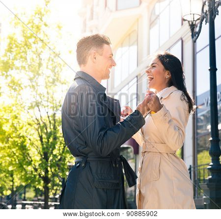 Laughing young couple flirting outdoors