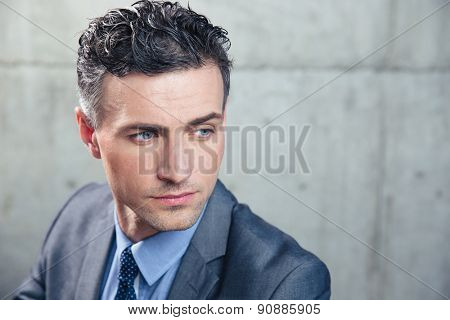 Portrait of a pensive businessman looking away over concrete wall