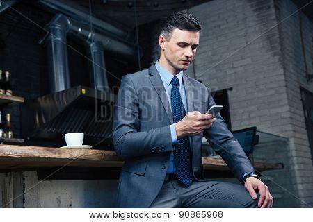 Handsome businessman using smartphone in cafe
